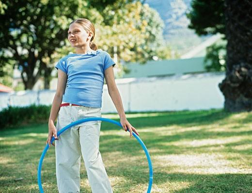 Stock Photo: 1491R-1079870 Girl (12-13) in garden,holding plastic hoop