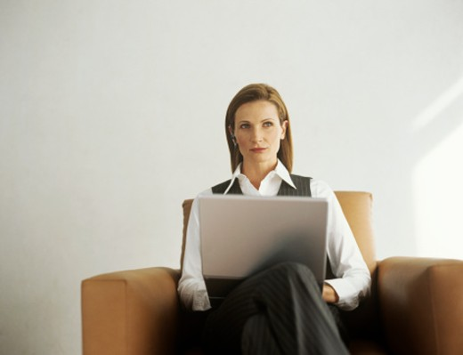 Stock Photo: 1491R-1080109 Businesswoman sitting in armchair with laptop