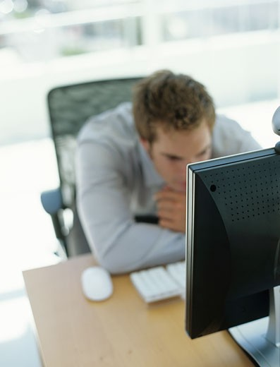 Man working at computer,focus on computer : Stock Photo