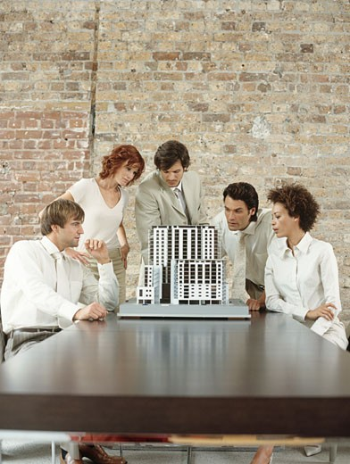 Business people looking at architect's model of building : Stock Photo