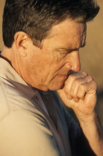 Mature man with hand on chin,looking down,profile,close-up : Stock Photo