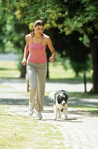 Stock Photo: 1491R-1081527 Woman jogging with dog,full length