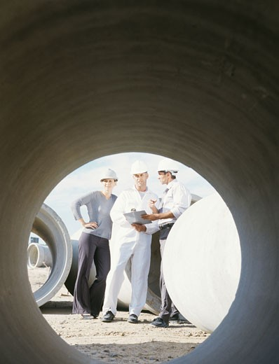 Stock Photo: 1491R-1081596 Men and woman in hard hats on construction site,view through pipe