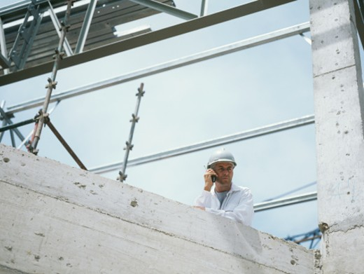 Stock Photo: 1491R-1081620 Construction worker using mobile phone on construction site