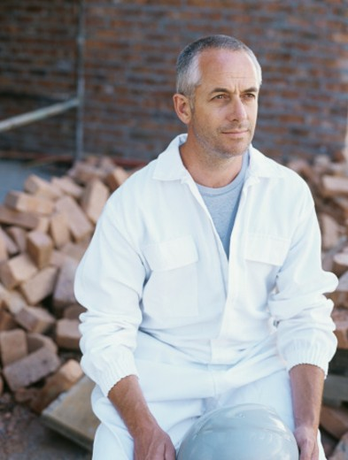 Stock Photo: 1491R-1081625 Man in protective work wear sitting on pile of bricks