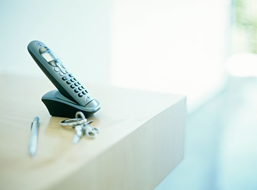 Stock Photo: 1491R-1081802 Cordless phone on table by keys and pen,differential focus