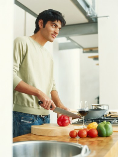 Young man cutting vegetables in kitchen : Stock Photo