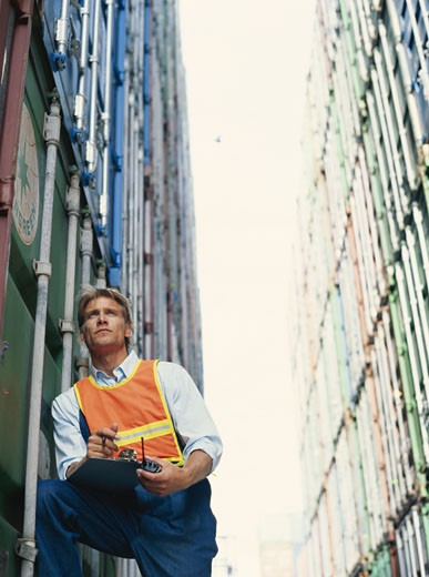 Stock Photo: 1491R-1082479 Manual worker standing at container terminal, low angle view