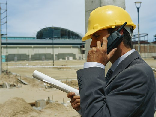 Engineer holding blue print and using walkie-talkie, side view, close-up : Stock Photo