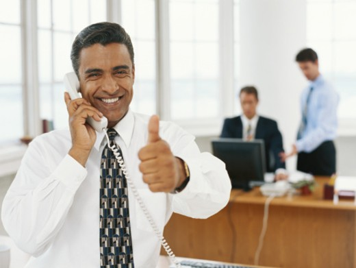 Businessman using telephone, giving thumbs up : Stock Photo
