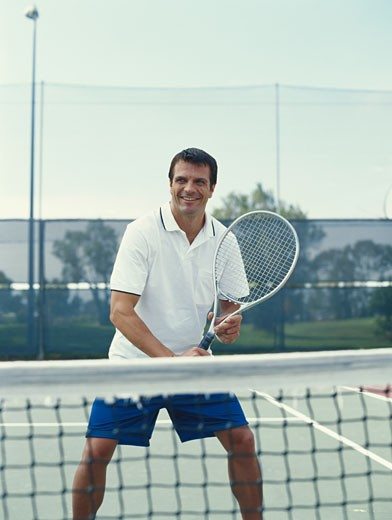 Young tennis player playing tennis, smiling : Stock Photo