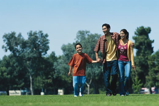 Stock Photo: 1491R-1083739 Boy (6-7) walking with parents in park, smiling
