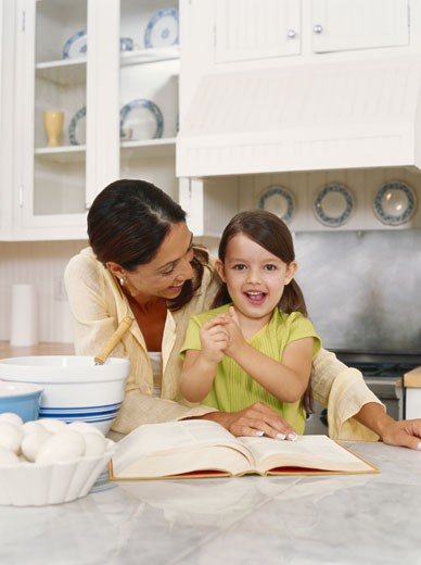 Mother and daughter (3-5) in kitchen, smiling : Stock Photo