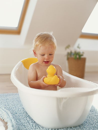 Baby boy (12-15 months) in bubble bath playing with rubber duck : Stock Photo