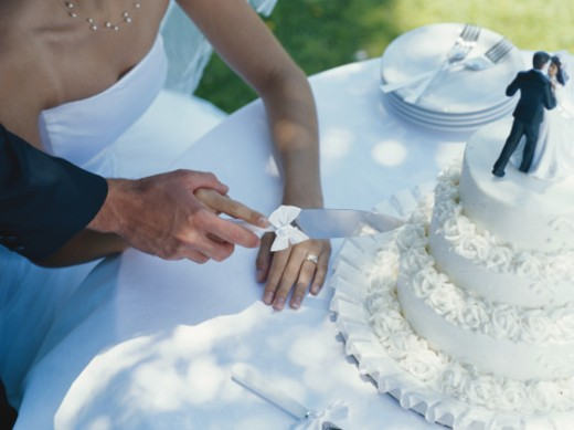 Stock Photo: 1491R-1084197 Newlywed couple cutting cake, elevated view