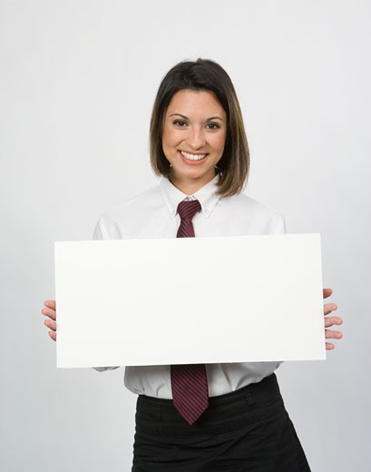 Stock Photo: 1491R-1084214 Portrait of young office worker holding blank sign