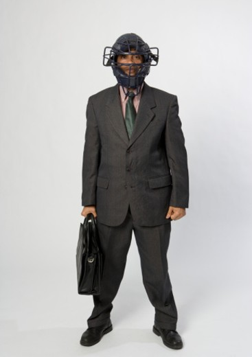 Stock Photo: 1491R-1084235 Portrait of young business man with briefcase wearing american football helmet
