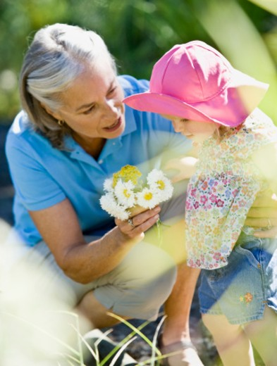 Senior woman giving flowers to baby girl (9-12 months) : Stock Photo