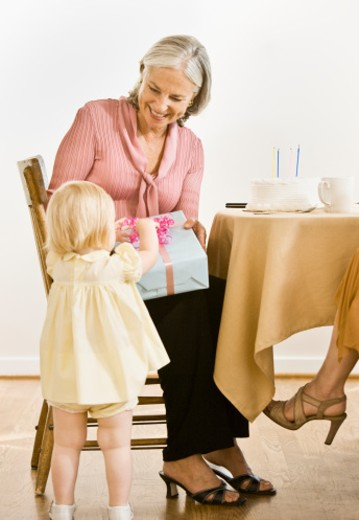 Stock Photo: 1491R-1084317 Baby granddaughter (9-12 months) giving gift to grandmother