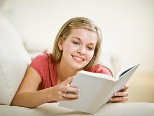 Young woman reading book on sofa : Stock Photo