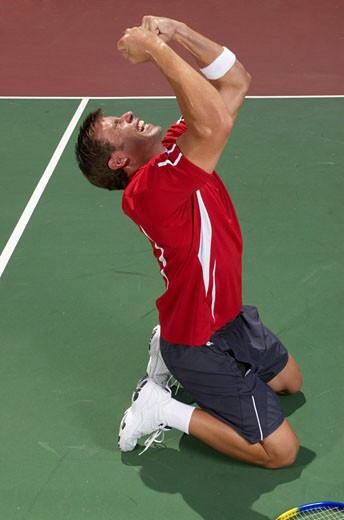 Young man kneeling on tennis court, screaming : Stock Photo