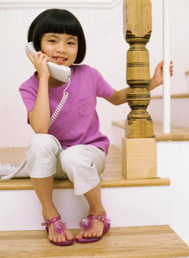Stock Photo: 1491R-1085821 portrait of a girl sitting on steps using the telephone