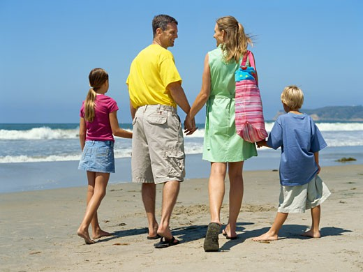 rear view of parents walking with their children on the beach : Stock Photo