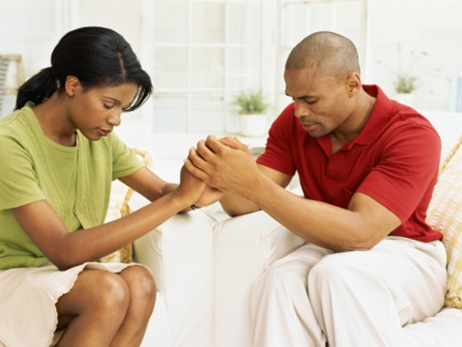 mid adult couple holding hands and praying : Stock Photo