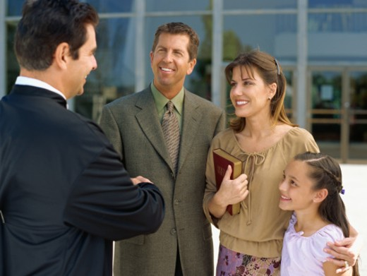 parents and their daughter talking to a priest : Stock Photo