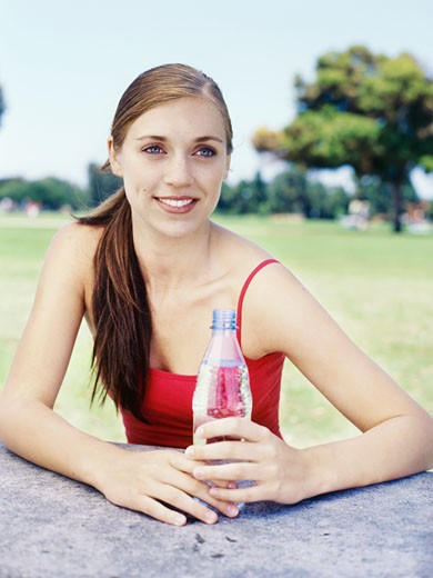 young woman sitting with a bottle of water : Stock Photo