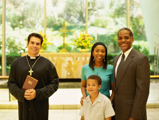 Stock Photo: 1491R-1086453 portrait of parents and their son standing with a priest
