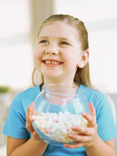 Stock Photo: 1491R-1086596 close-up of a girl holding a bowl of candies