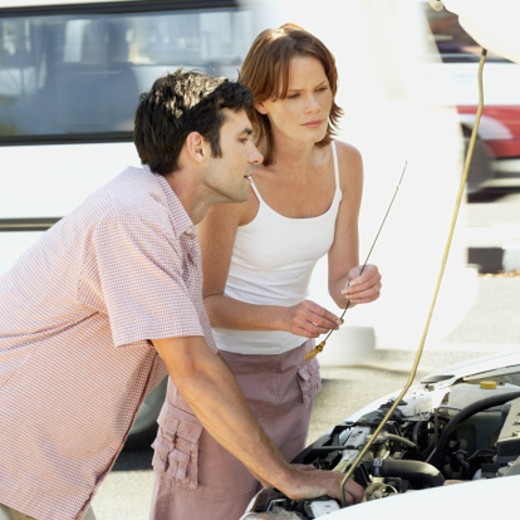 Stock Photo: 1491R-1086655 young couple checking the oil level of a car