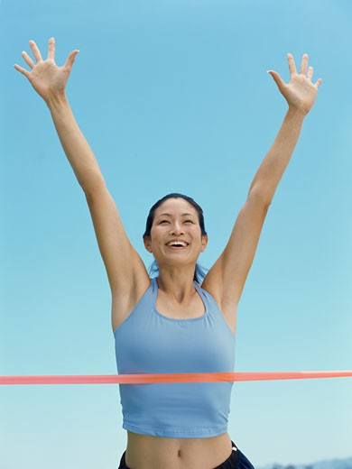 low angle view of a female athlete crossing the finish line : Stock Photo