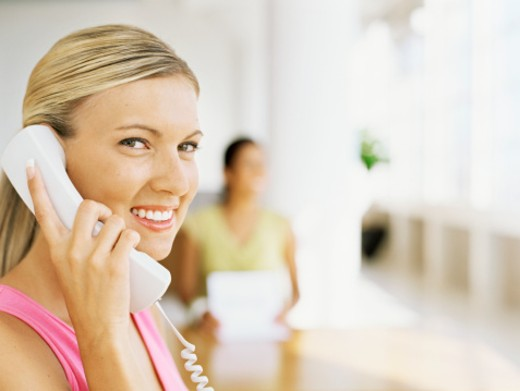 side profile of a young woman talking on the telephone : Stock Photo