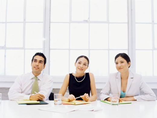 Stock Photo: 1491R-1087143 businessman and two businesswomen sitting side by side in an office