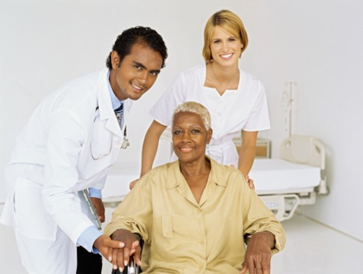 portrait of a male doctor and a female nurse with a patient on a wheelchair : Stock Photo