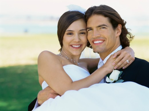 portrait of a groom carrying his bride : Stock Photo