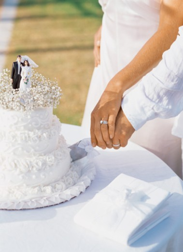 mid section view of a newlywed couple cutting their wedding cake : Stock Photo