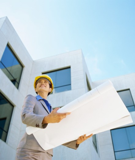low angle view of a female architect holding blueprints : Stock Photo