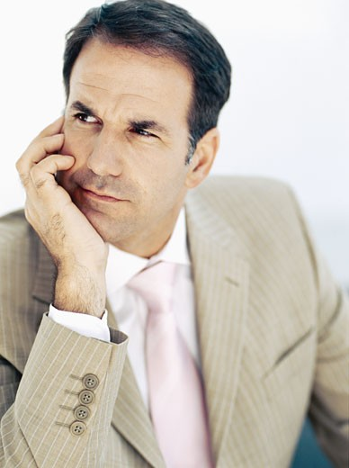 Stock Photo: 1491R-1088807 close-up of a businessman thinking with his hand on his chin