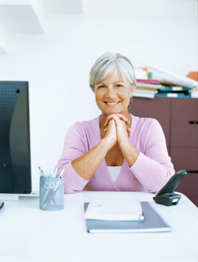 portrait of a businesswoman smiling with her hands clasped : Stock Photo