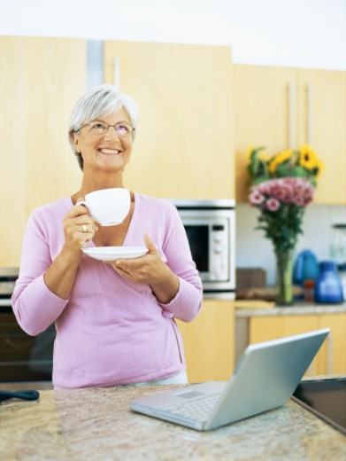 businesswoman holding a cup of tea in the kitchen : Stock Photo