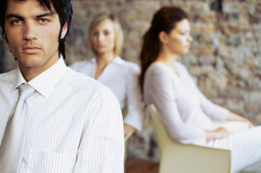 Stock Photo: 1491R-1089784 portrait of a businessman with two businesswomen sitting behind him