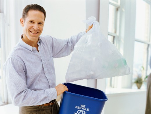 portrait of a mid adult man holding a garbage bin and a garbage bag : Stock Photo