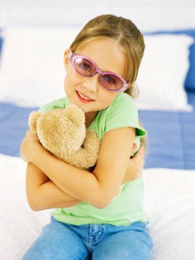 portrait of a girl wearing sunglasses and hugging a teddy bear : Stock Photo
