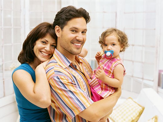 portrait of a mid adult couple carrying their daughter : Stock Photo