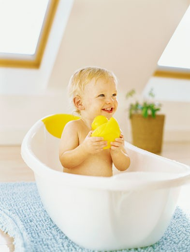 baby boy in a bathtub holding a rubber duck : Stock Photo