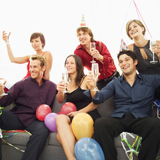 Stock Photo: 1491R-1092266 group of young people at a party sitting on a sofa with champagne
