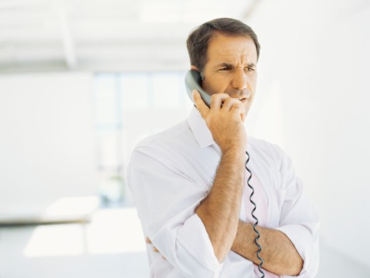 Stock Photo: 1491R-1092432 businessman talking on a telephone in an office